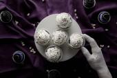 top view dekoratív kéz közelében stand finom Halloween cupcakes lila ruhán