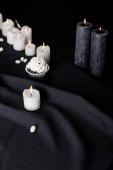tasty Halloween cupcake with white cream near burning candles on black background