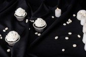 Photo tasty Halloween cupcakes with white cream near burning candles on black cloth