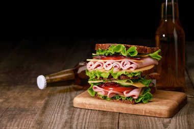 Fresh sandwich with lettuce, ham, cheese, bacon and tomato on wooden cutting board near bottles of beer isolated on black stock vector