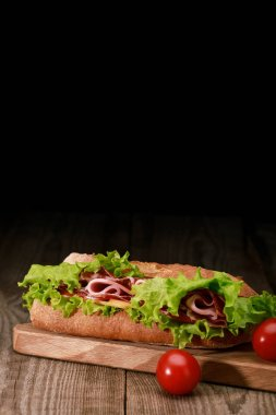fresh sandwich with lettuce, ham, cheese, bacon on wooden cutting board with cherry tomatoes isolated on black