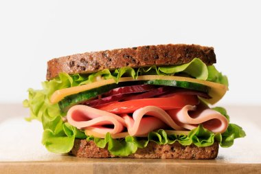 fresh sandwich with lettuce, ham, cheese, bacon and tomato on wooden cutting board isolated on white