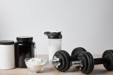 Protein shake in sports bottle near jars and dumbbells on white stock vector