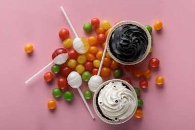 top view of delicious Halloween cupcakes, lollipops and bonbons on pink background