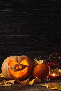 carved spooky Halloween pumpkin, autumnal leaves and burning candle on wooden rustic table on black background