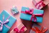 vrchní pohled na barevné dárkové krabice s saténovými stuhami na růžovém pozadí