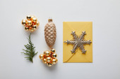 Fotografia top view of shiny Christmas decoration, fir branch and envelope on white background