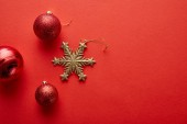 top view of shiny Christmas baubles and golden snowflake on red background