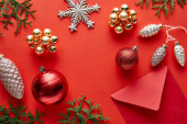 top view of shiny Christmas decoration, envelope and thuja on red background