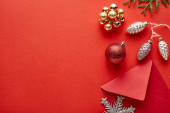 top view of shiny Christmas decoration, envelope and thuja on red background with copy space