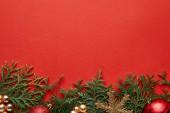 Rand der glänzenden Weihnachtsdekoration auf grünen Thuja-Zweigen auf rotem Hintergrund mit Kopierraum