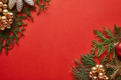 top view of shiny Christmas decoration on green thuja branches on red background with copy space