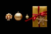 flat lay with shiny golden Christmas gift with red ribbon and snowflake near baubles isolated on black