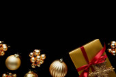 top view of shiny golden Christmas gift with red ribbon and snowflake near baubles isolated on black