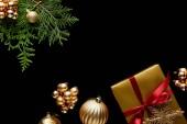 Fényképek felső nézet fényes arany karácsonyi dekoráció, zöld thuja ágak és ajándék doboz elszigetelt fekete