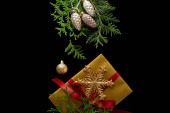 top view of shiny golden Christmas decoration, green thuja branches and gift box isolated on black