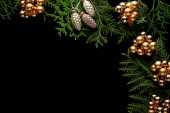 vrchní pohled na lesklé zlaté vánoční dekorace na zelené větve thuja izolované na černé s kopírovacím prostorem