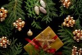 vrchní pohled na lesklé zlaté vánoční dekorace, zelené větve thuja a dárkové krabice izolované na černé