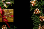 top view of shiny golden Christmas decoration, green thuja branches and gift isolated on black with copy space