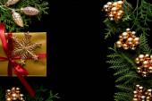 Fotografie vrchní pohled na lesklé zlaté vánoční dekorace, zelené větve thuja a dárek izolované na černé s kopírovacím prostorem