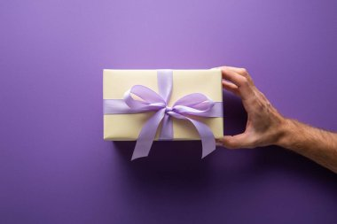 Cropped view of man holding gift box with violet ribbon on purple background stock vector