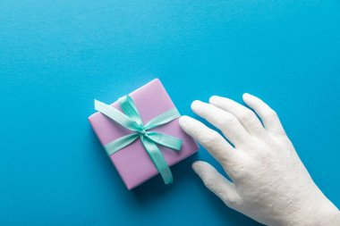 Cropped view of painted hand near violet gift box on blue background stock vector