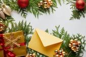 Fényképek felső nézet fényes arany karácsonyi dekoráció, ajándék és boríték zöld thuja ágak elszigetelt fehér