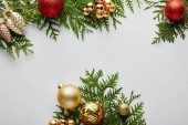 Photo top view of shiny golden and red Christmas decoration on green thuja branches isolated on white