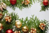 Fotografie vrchní pohled na lesklé zlaté a červené vánoční dekorace na zelené větve thuja izolované na bílém