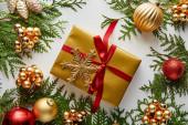 Fotografie vrchní pohled na lesklé zlaté a červené vánoční ozdoby na zelené větve thuja, zabalený dárek se sněhovou vločkou izolované na bílé