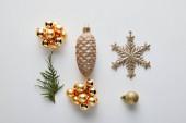 lapos feküdt fényes arany karácsonyi dekoráció és zöld thuja ág elszigetelt fehér
