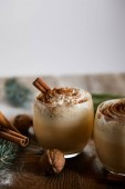 delicious eggnog cocktail with whipped cream, cinnamon sticks and wallnuts on wooden table isolated on grey