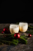 traditional eggnog cocktail near spruce branch and Christmas balls on dark marble surface isolated on black