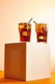 Blick auf Cocktails cuba libre in Gläsern mit Strohhalmen auf Würfel