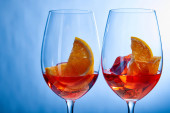 Cocktails Aperol Spritz mit Eiswürfeln in Gläsern auf blauem Hintergrund