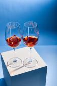 Aperol Spritz mit Eiswürfeln in Gläsern auf blauem Hintergrund