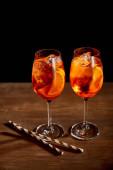 Aperol Spritz in Gläsern mit Strohhalmen auf Holztisch