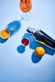 vrchní pohled na Aperol Spritz, pomeranče, třepačka, kostky ledu a odměrka na modrém pozadí