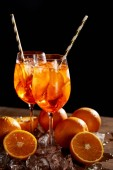 Aperol Spritz in glasses, oranges and ice cubes on black background
