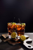 cocktails cuba libre in glasses with straws and limes on black background