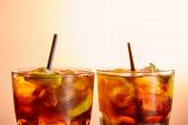 Cocktails cuba libre in Gläsern mit Strohhalmen auf beigem Hintergrund