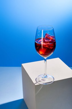 cocktail Aperol Spritz with ice cubes in glass on blue background