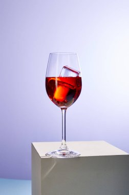 cocktail Aperol Spritz with ice cubes in glass on purple background