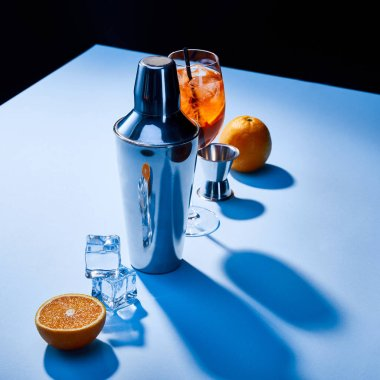 Cocktail Aperol Spritz, oranges, shaker, ice cubes and measuring cup on blue background stock vector