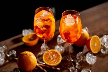 High angle view of Aperol Spritz in glasses, oranges and ice cubes on black background stock vector