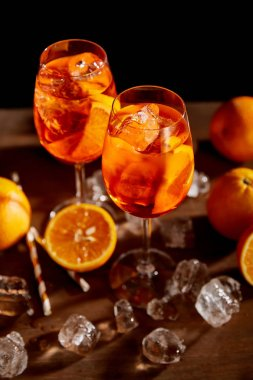 Selective focus of Aperol Spritz in glasses, oranges and ice cubes on black background stock vector