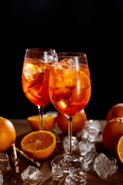 Aperol Spritz in glasses, oranges and ice cubes on black background stock vector