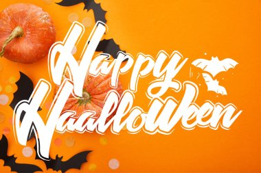 top view of pumpkin, bats and confetti on orange background with happy Halloween illustration