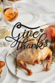 Fotografie grilled turkey near glasses with white wine and lemon water on white tablecloth with give thanks illustration