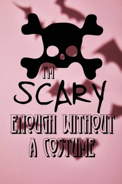 shadow of flying bats on pink background with i am scary enough without a costume illustration